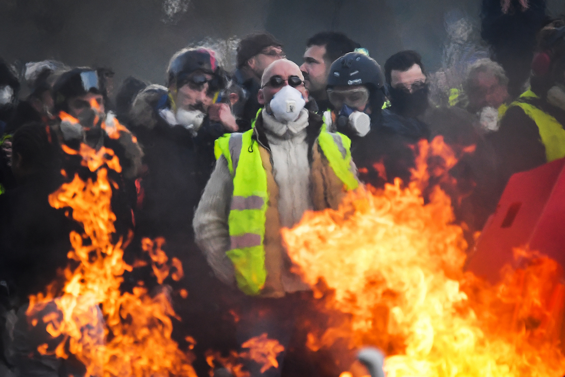 """Protesters stand behind a barricade set on fire during an anti-government demonstration called by the """"yellow vests"""" (gilets jaunes) movement on January 19, 2019, in Angers, western France. - France's """"yellow vests"""" took to the streets on January 19 for a 10th straight weekend of anti-government protests, despite attempts by the president to channel their anger into a series of town hall debates. (Photo by LOIC VENANCE / AFP)"""