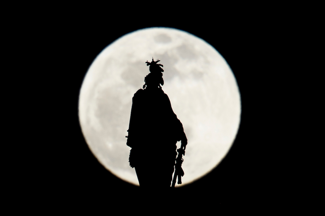 The Statue of Freedom on top of the US Capitol dome is seen silhouetted against the super moon on January 20, 2019 in Washington, DC. (Photo by Brendan Smialowski / AFP)