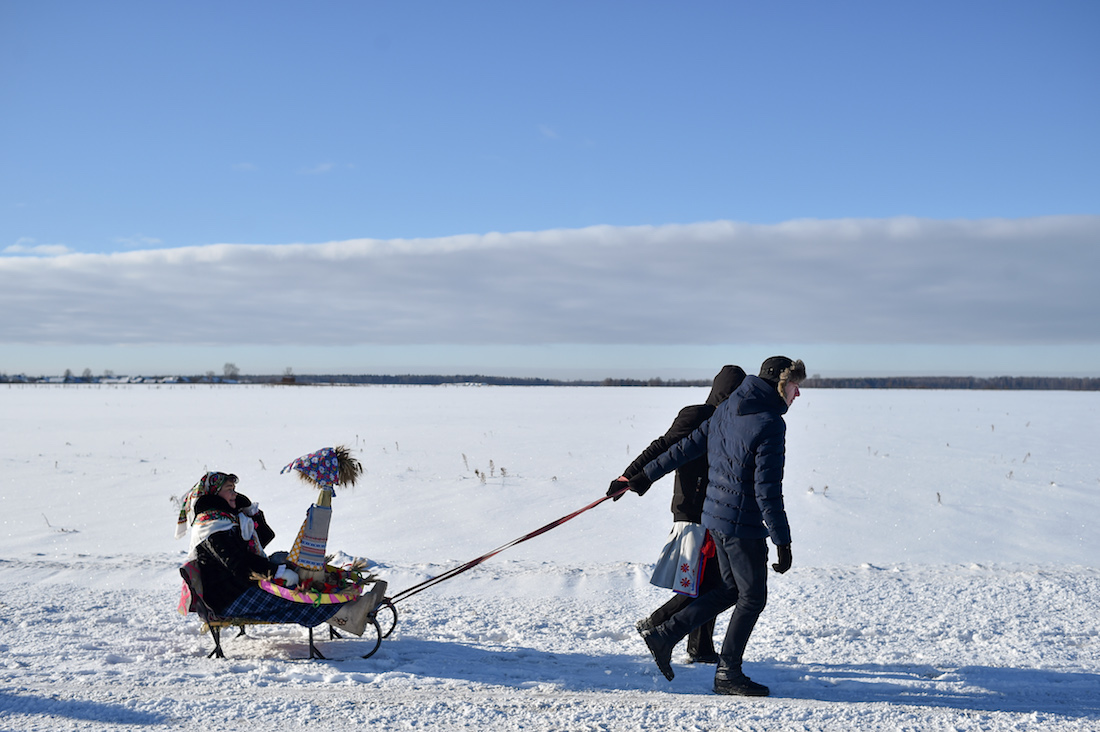 """Belarus' villagers celebrate the """"Pull the Kalyada up on the oak"""" rite in the village of Martsiyanauka, some 110 kilometers east of Minsk, on January 21, 2019. - Participants pull the Kalyada, a sheaf of straw on a wooden wheel, up on an oak tree to bring a rich harvest. (Photo by Sergei GAPON / AFP)"""
