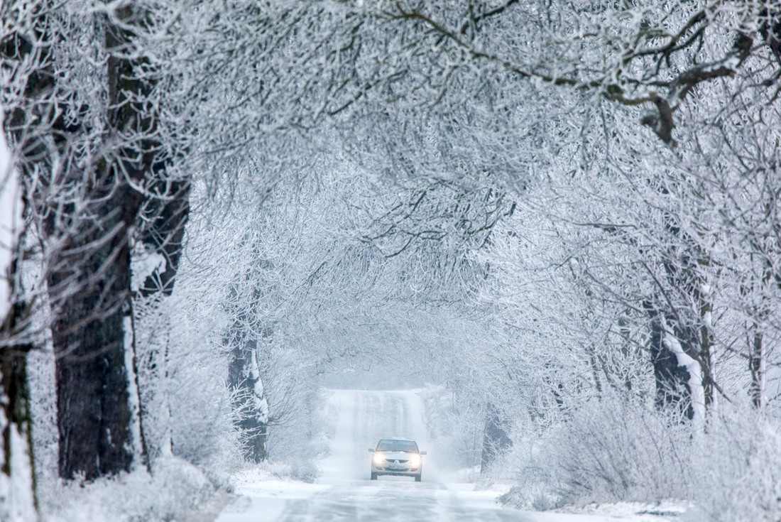 A picture taken on January 21, 2019 in Gadebusch shows a car driving on a snow-covered road. (Photo by Jens B¸ttner / dpa / AFP) / Germany OUT