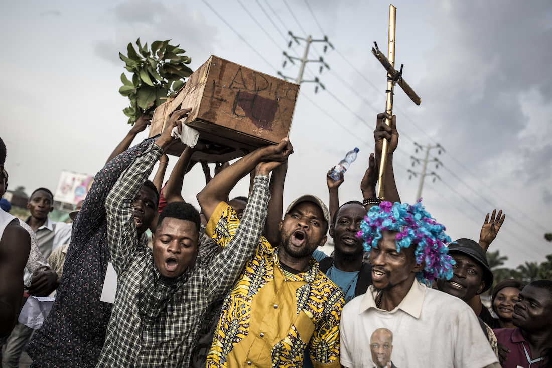 """Supporters of Martin Fayulu, the runner up in the Democratic Republic of the Congo's(DRC'S) elections, hold up a coffin with """"Good Bye Felix"""" as they protest in the street on January 21, 2019 in Kinshasa, against the decision of Felix Tshisekedi as president of the DRC. - DR Congo was on January 21, 2019 making plans to install Felix Tshisekedi as its new president this week after a long and bitter election whose outcome was disputed by the runner-up and shunned by many western nations. The ceremony, which was scheduled for January 22, but looks increasingly likely to happen later in the week, will see the 55-year-old sworn in as president, replacing Joseph Kabila who has ruled DR Congo since 2001. (Photo by John WESSELS / AFP)"""