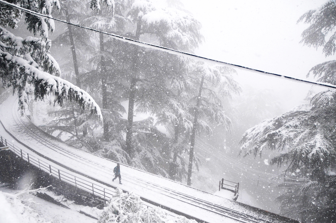 A man walks on a railway track during snowfall in the northern Indian hill town of Shimla on January 22, 2019. (Photo by STR / AFP)