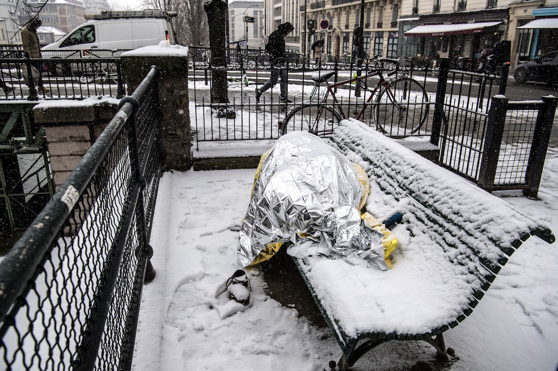 A homeless man sleeps under blankets on a bench as snow falls over in Paris on January 22, 2019. (Photo by Christophe ARCHAMBAULT / AFP)