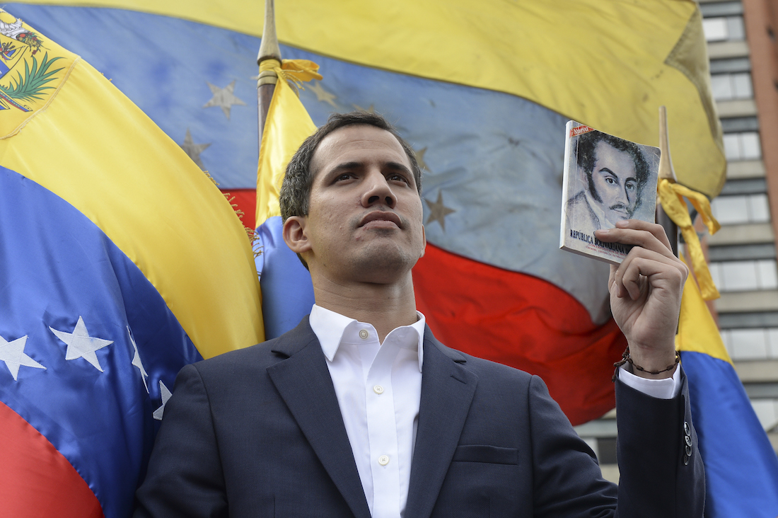 """Venezuela's National Assembly head Juan Guaido declares himself the country's """"acting president"""" during a mass opposition rally against leader Nicolas Maduro, on the anniversary of a 1958 uprising that overthrew military dictatorship in Caracas on January 23, 2019. - Moments earlier, the loyalist-dominated Supreme Court ordered a criminal investigation of the opposition-controlled legislature. """"I swear to formally assume the national executive powers as acting president of Venezuela to end the usurpation, (install) a transitional government and hold free elections,"""" said Guaido as thousands of supporters cheered. (Photo by Federico PARRA / AFP)"""