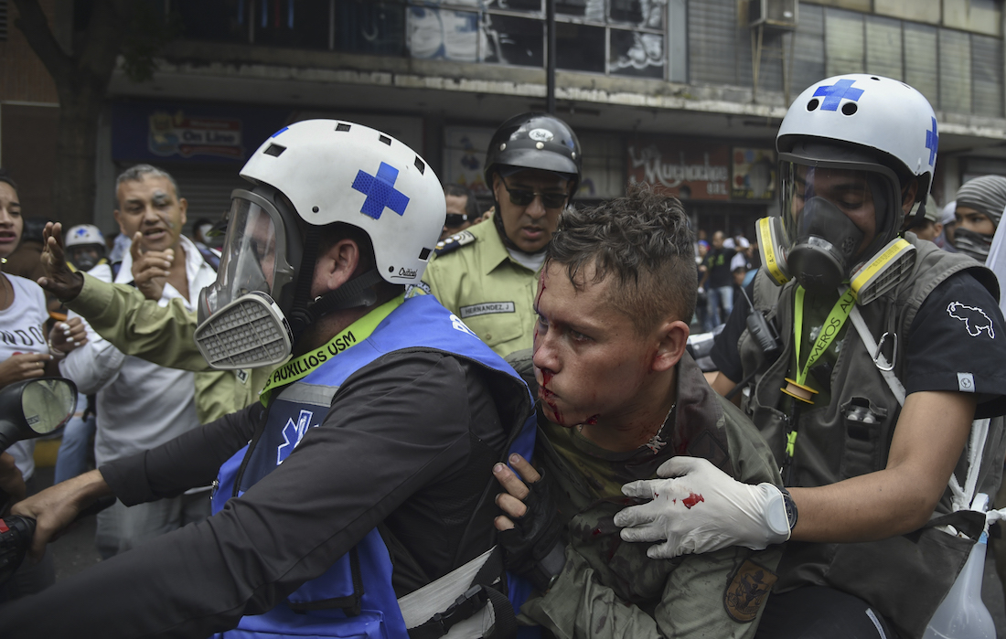 """Paramedics rescue a wounded member of the Bolivarian National Guard during clashes with opposition demonstrators, in a protest against the government of President Nicolas Maduro on the anniversary of the 1958 uprising that overthrew the military dictatorship, in Caracas on January 23, 2019. - Venezuela's National Assembly head Juan Guaido declared himself the country's """"acting president"""" on Wednesday during a mass opposition rally against leader Nicolas Maduro. (Photo by YURI CORTEZ / AFP)"""