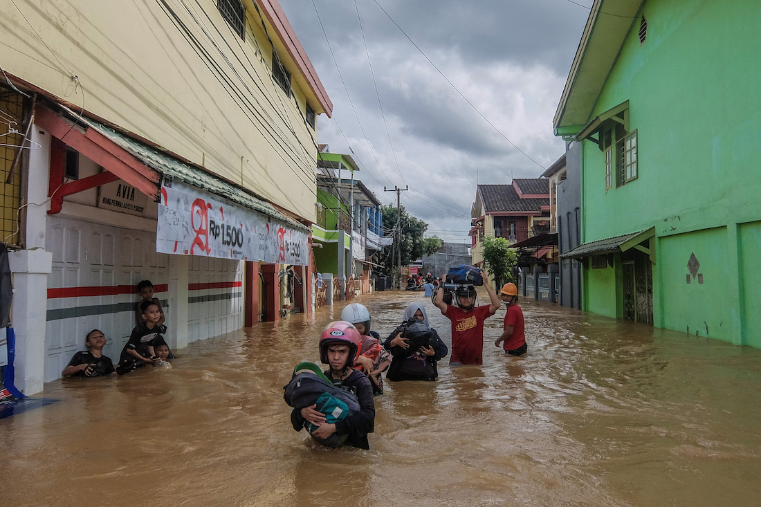 This picture taken on January 23, 2019 shows residents evacuating their homes in Makassar as heavy rain and strong winds pounded the southern part of Sulawesi island, swelling rivers that burst their banks and inundating dozens of communities in nine southern districts. - The death toll from flash floods and landslides in Indonesia jumped to 26, a disaster agency official said on January 24, as rescuers race to find still-missing victims. (Photo by STR / AFP)