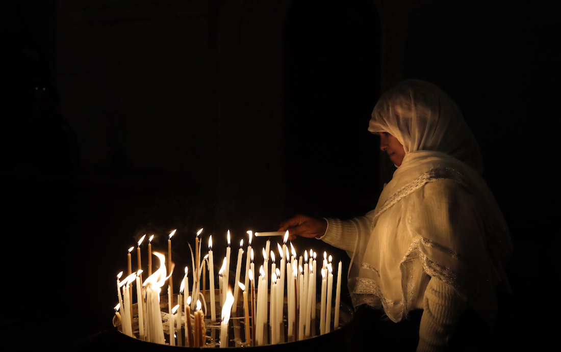 A Christian worshipper lights a candle inside the Church of the Holy Sepulchre in  Jerusalem's Old City, on January 24, 2019. (Photo by THOMAS COEX / AFP)