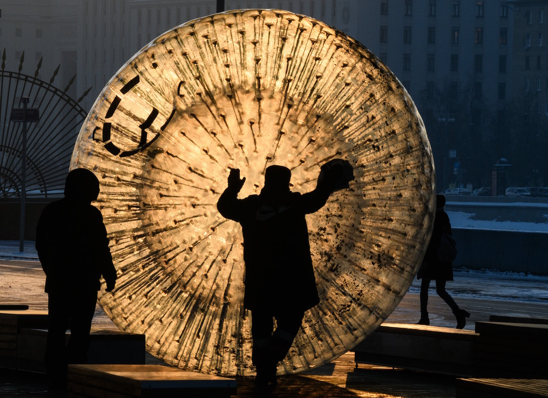 A man cleans a zorb ball outside the Gorky Park at sunset in Moscow on January 24, 2019, with the air temperatures at -16 degrees Celsius. (Photo by Mladen ANTONOV / AFP)