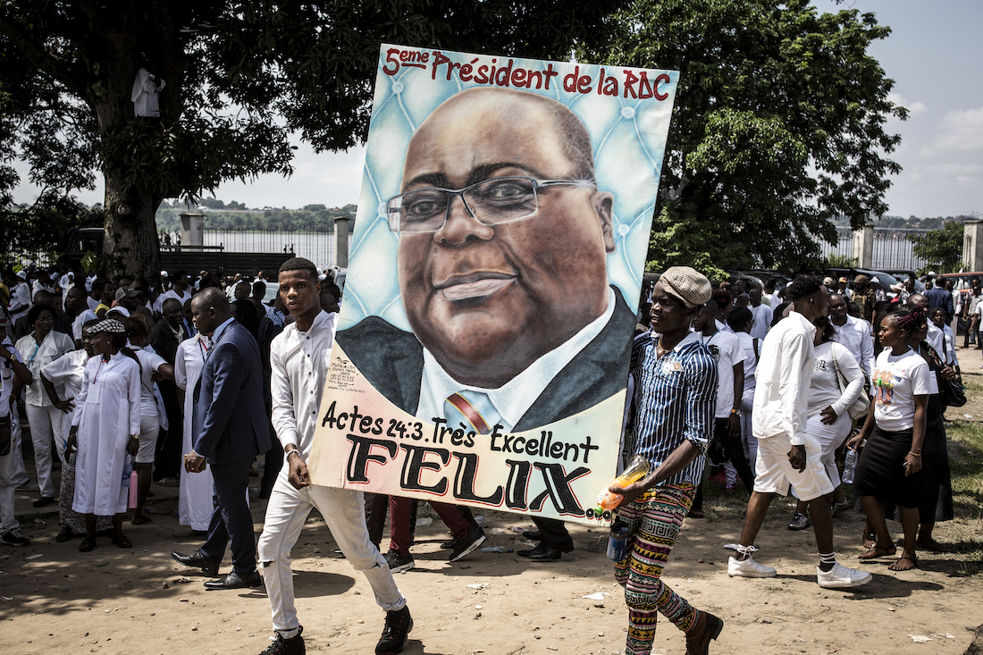Supporters of new elected President of the Democratic Republic of Congo Felix Tshisekedi hold his portrait and cheer during his Presidential Inauguration on January 24, 2018 in Kinshasa. - Tshisekedi took the oath of office before receiving the national flag and a copy of the constitution from outgoing president Joseph Kabila, stepping aside after 18 years at the helm of sub-Saharan Africa's biggest country, marking the country's first-ever peaceful handover of power after chaotic and bitterly-disputed elections. (Photo by John WESSELS / AFP)