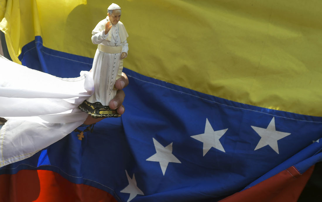 A faithful holds a souvenir doll of Pope Francis next to a Venezuelan national flag, while gathering alongside the street to see him, during the World Youth Days in Panama City on January 24, 2019. - Pope Francis will on Thursday formally open World Youth Day celebrations which have drawn around 200,000 young people from around the world to Panama where he is expected to defend Central American migrants and human rights. (Photo by Raul Arboleda / AFP)