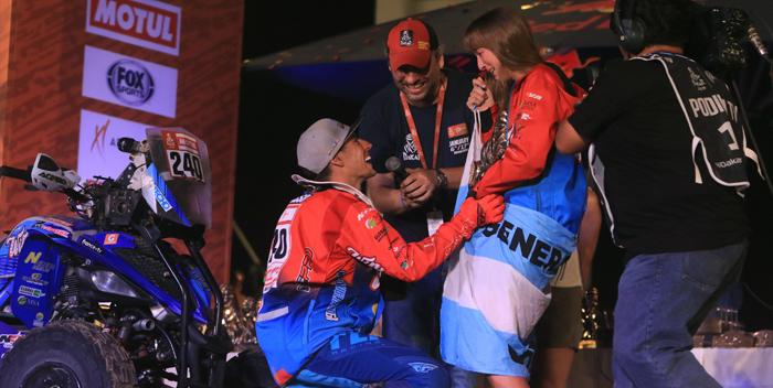 -FOTODELDIA- PR01. PISCO (PERÚ), 17/01/2019.- El piloto argentino Nicolás Cavigliasso (izq) pide matrimonio a su novia (c) tras proclamarse campeón en la categoría de quads del Rally Dakar 2019, este jueves, en Pisco (Perú). El Dakar 2019 fue la primera edición del rally más duro del mundo que se disputó de principio a fin en un único país, con diez etapas en Perú del 7 al 17 de enero y un recorrido de más de 5.000 kilómetros, de los que casi 3.000 eran cronometrados. EFE/Sebastián Castañeda