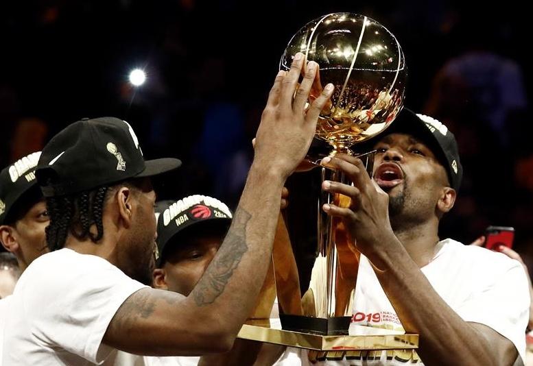 El jugador de los Raptors de Toronto, Serge Ibaka (d) sostiene el Trofeo de la NBA Larry O'Brien, junto a su compañero Kawhi Leonard (i) tras ganar el torneo en el sexto partido de las finales de la NBA entre Toronto Raptors y Golden State Warriors