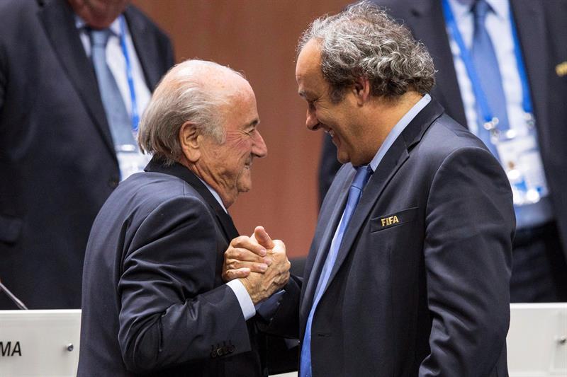 Foto de archivo del entonces presidente de la UEFA Michel Platini (dcha) mientras estrecha la mano al responsable de la FIFA Joseph S. Blatter (izq) tras su elección como presidente en Zúrich (Suiza) el 29 de mayo de 2015. Foto: EFE